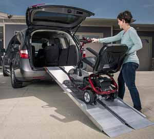 Suitcase Portable Wheelchair Ramps loading scooter into SUV.